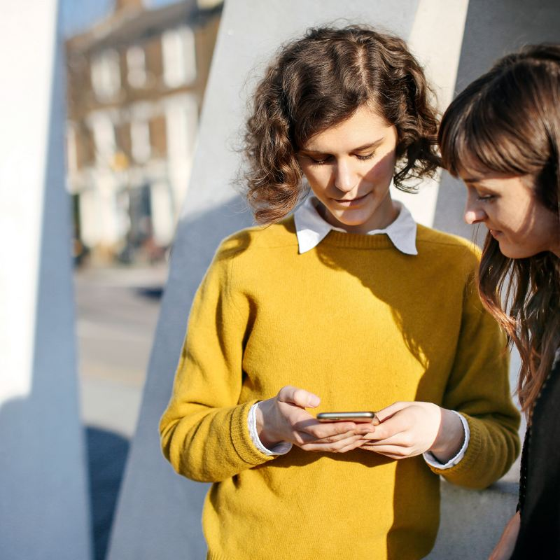 Zwei Frauen blicken zusammen auf ein Smartphone.