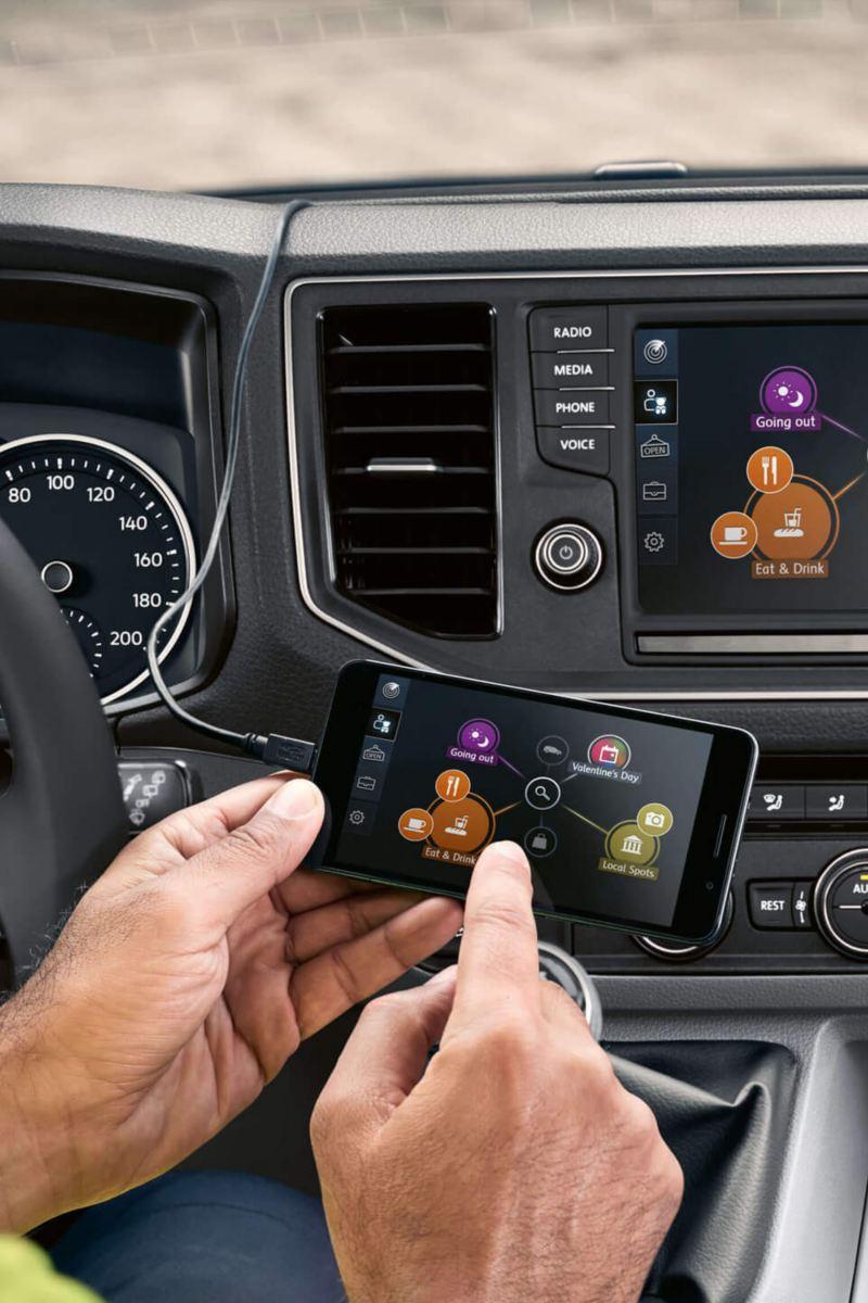 Bestuurder gebruikt navigatiesysteem door middel van zijn smartphone