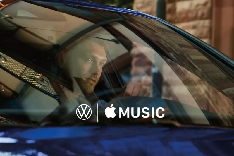 VW Golf driver looking through the front window, Volkswagen and Apple logo displayed on the image