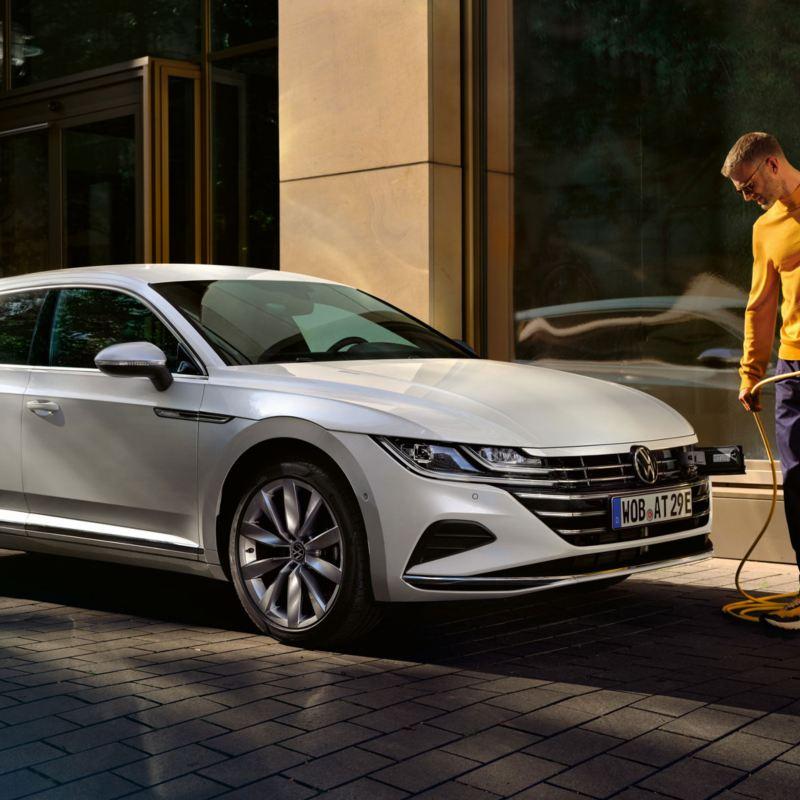 VW Arteon eHybrid steht vor einem Bürogebäude neben einer Ladesäule, ein Mann hat das Stromkabel der Ladesäule in der Hand.