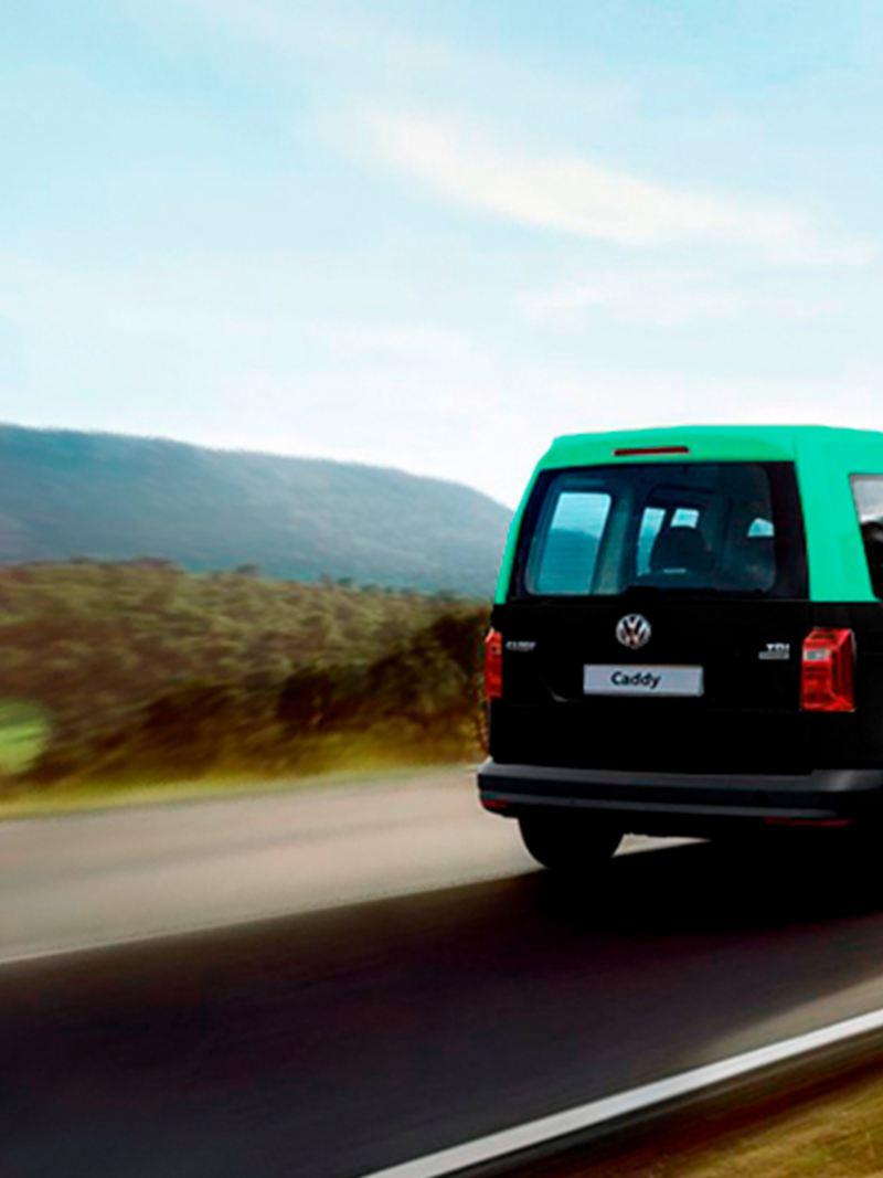 Carrinha Caddy adaptada para Táxi a percorrer uma estrada.