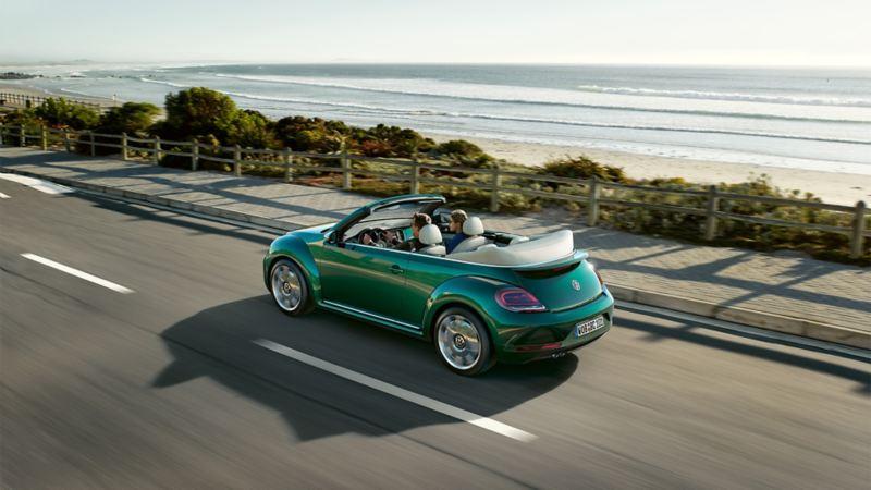 VW Cabrio fährt auf Küstenstraße