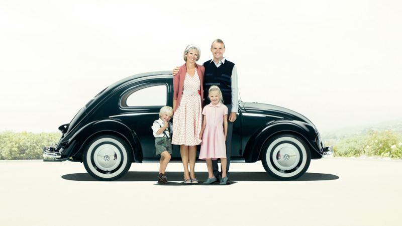 Famiglia in posa davanti a vecchio Maggiolino VW nero