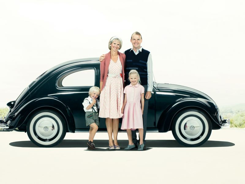 A family standing in front of a black VW Beetle