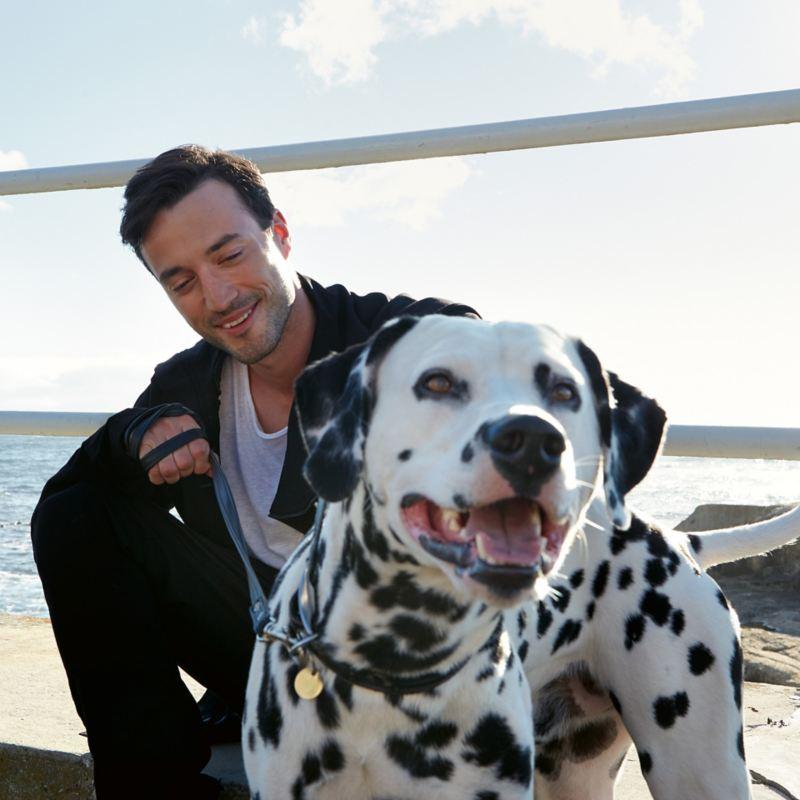 Mies koiran kanssa rannalla