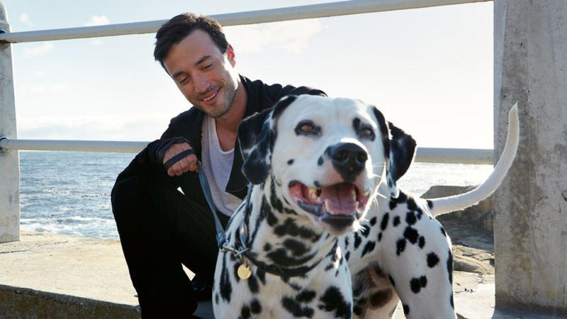 Man med en hund vid en strand