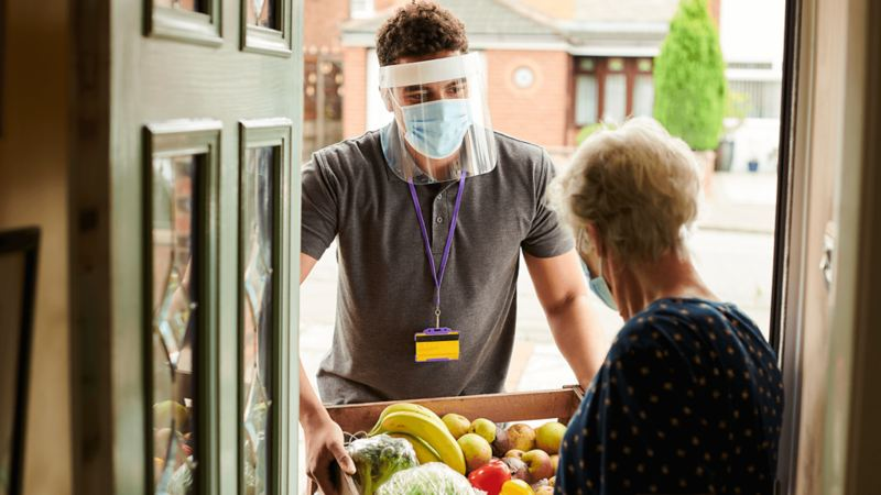 A volunteer in a face mask delivering groceries to an elderly woman.