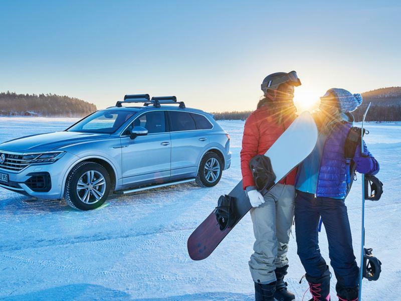 Una Volkswagen parcheggiata su un campo innevato con pneumatici invernali e una coppia di ragazzi vicino.