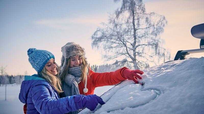deux filles dessinent avec la neige tombée sur une voiture