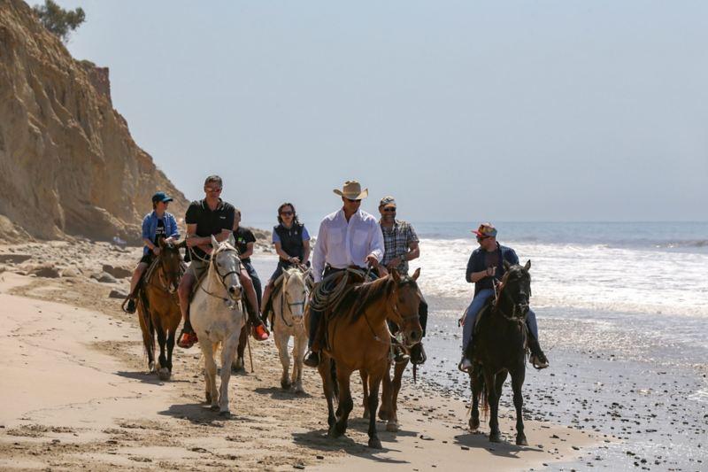 Te paard, op het strand