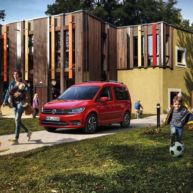 Un Volkswagen Caddy parcheggiato sul vialetto di un prato con una famiglia felice e bambini che giocano.