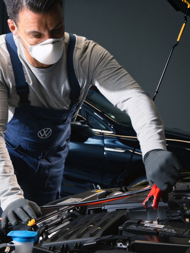 Un tecnico di Volkswagen Service intento a collegare il morsetto di una batteria.