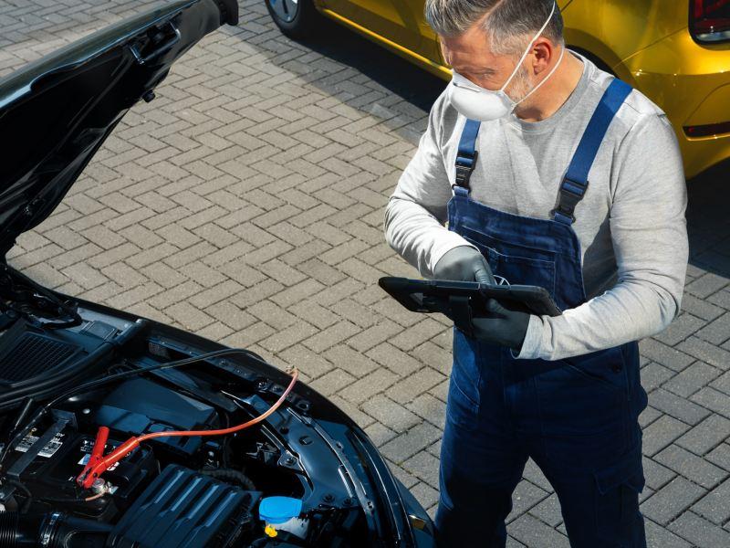 Un addetto controlla la batteria di un'auto Volkswagen.