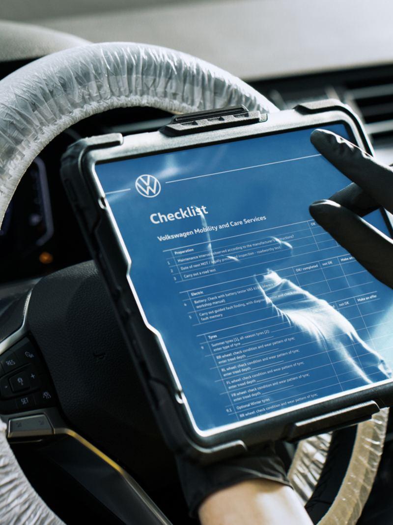 Un tecnico Volkswagen Service mentre guarda una checklist su un tablet all'interno di un'auto.