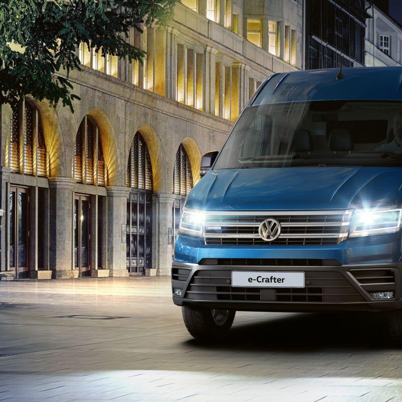 Volkswagen e-Crafter di notte, mentre attraversa una città illuminata a giorno.