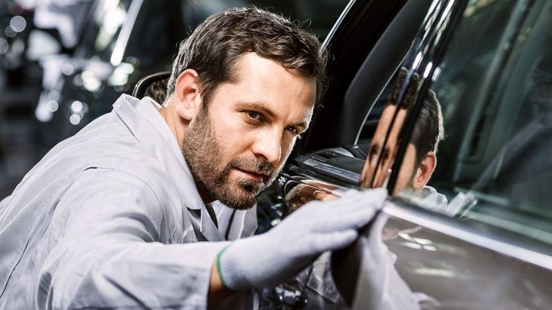 Ein Mann prüft die Karosserie eines Fahrzeugs