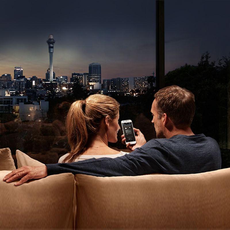uomo e donna consultano lo smartphone seduti sul divano davanti alla finestra dove si vede città di notte