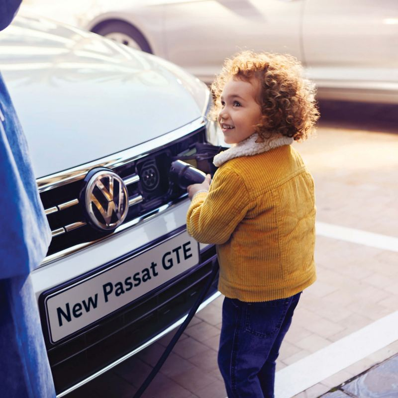 A young child connecting a plug to the front of a Volkswagon Passat GTE