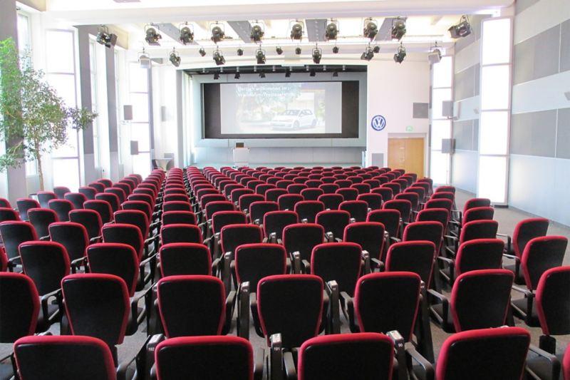 Großer Konferenzraum mit roter Bestuhlung und großer Leinwand im Bühnenbereich