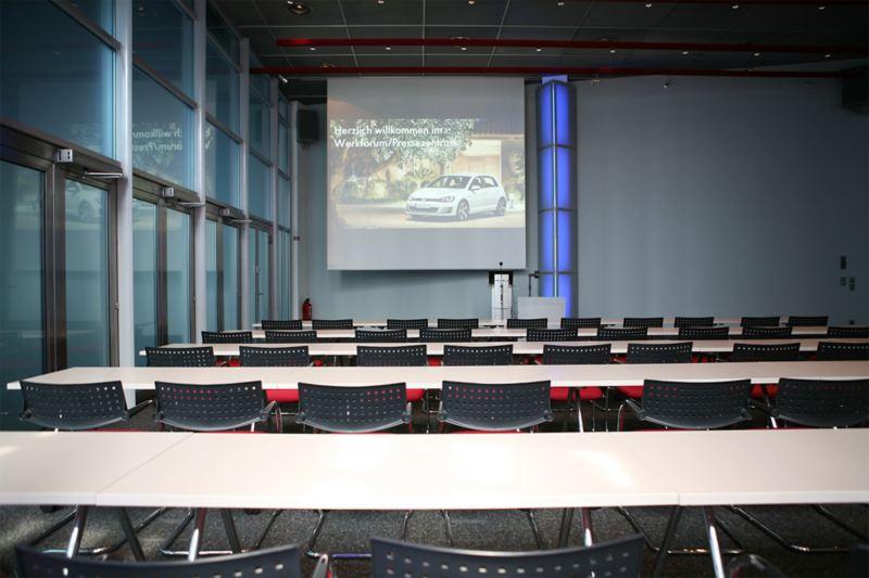 Ein Presseraum mit langen Tischreihen und Leinwand