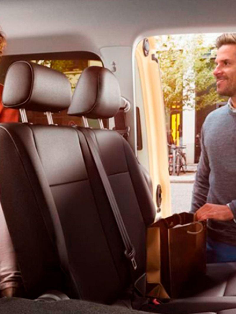 Pessoas a entrar na carrinha de passageiros VW Caddy.