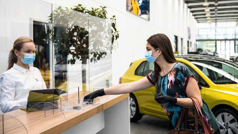 Una donna consegna le chiavi dell'auto ad un addetto presso un centro Volkswagen Service senza alcun contatto.