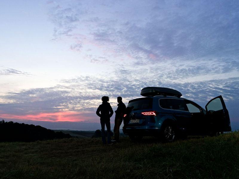 Ein Paar vor ihrem Fahrzeug bei Sonnenaufgang