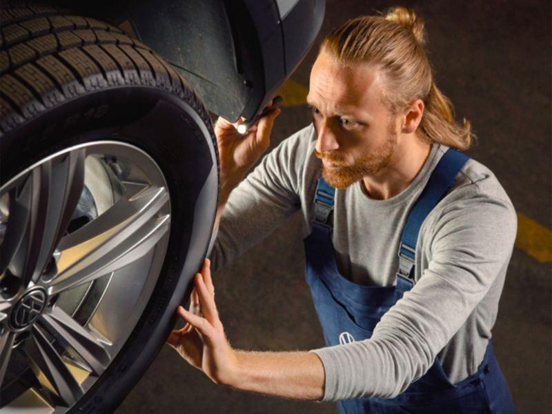 Un addetto controlla la pressione e lo spessore del battistrada degli pneumatici.