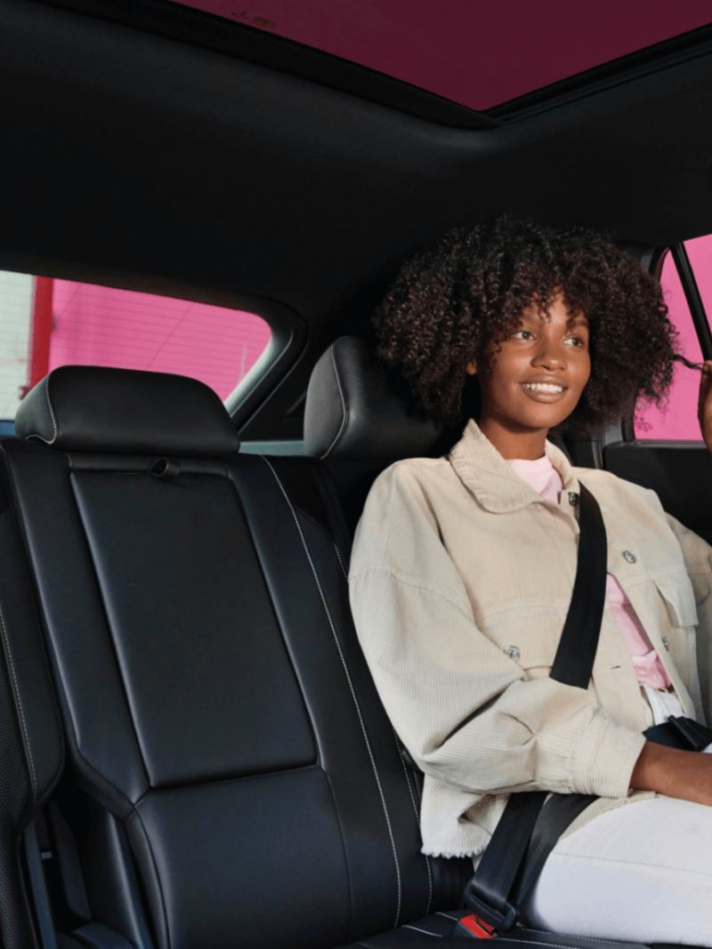 A black woman at the back seat of VW Cross Sport