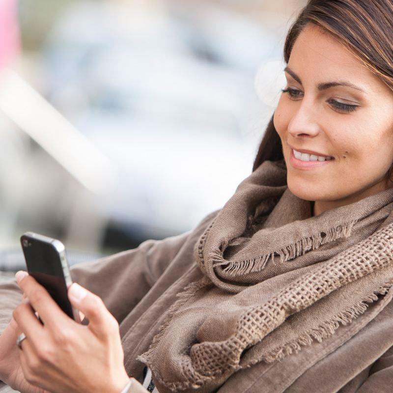 Kvinna som håller och kollar på sin mobiltelefon