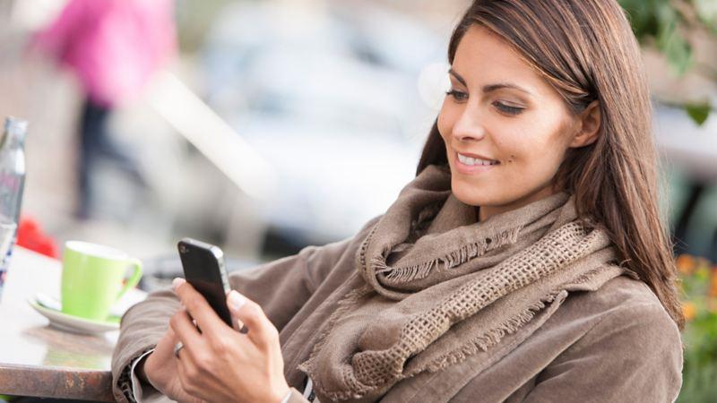 Frau reserviert am Smartphone Leasing-Fahrzeug