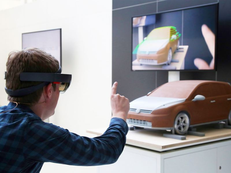 A man wearing VR glasses standing in front of a model car