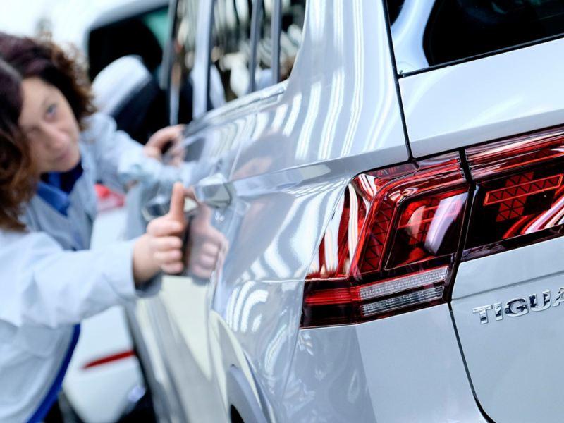 Eine Frau bei der Qualitätsprüfung eines Fahrzeugs