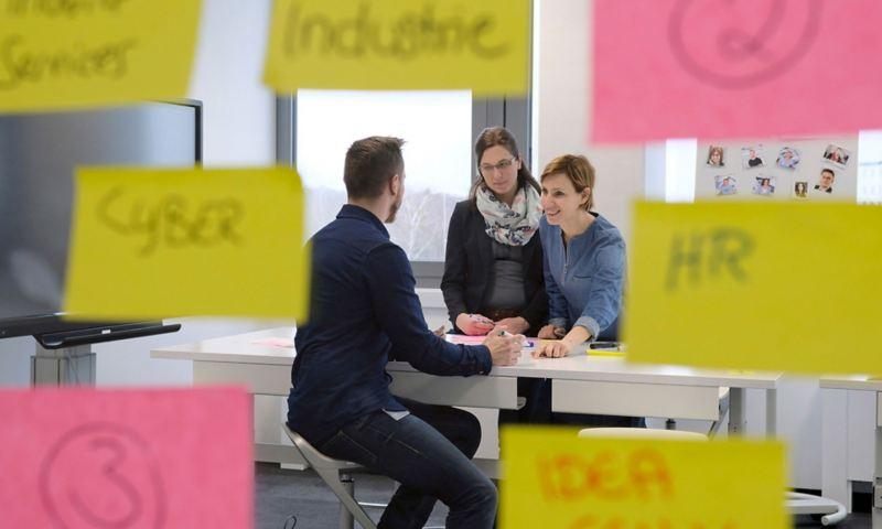 Drei Mitarbeiter arbeiten in einem Besprechungsraum