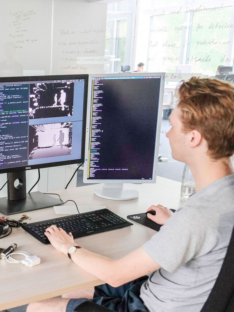 A man working on a software program in front of two monitors