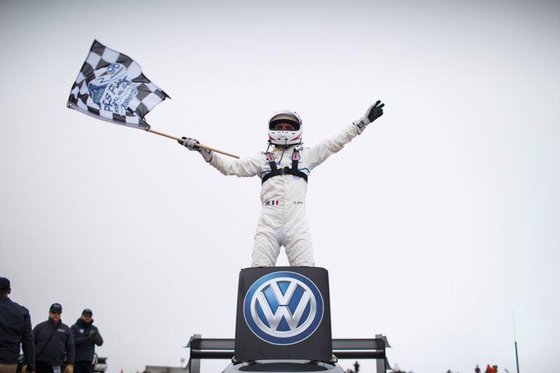 Romain Dumas waves the checkered flag