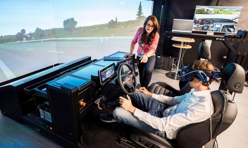 Eine Frau assistiert einem Mann, der mit VR-Brille in einem Fahrsimulator sitzt