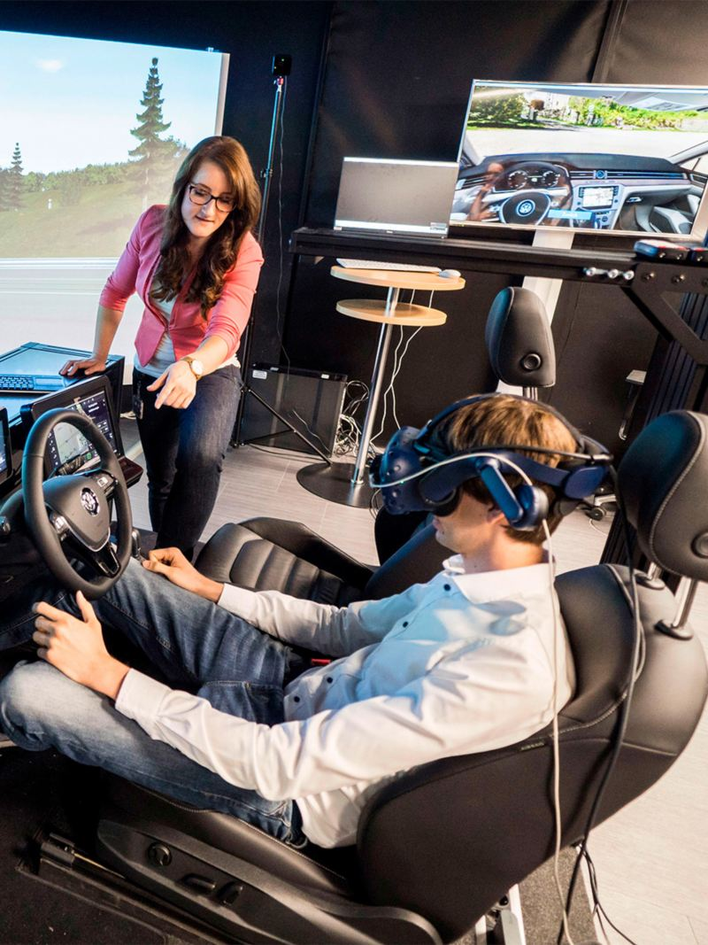 A woman assisting a man wearing VR glasses sitting in a driving simulator