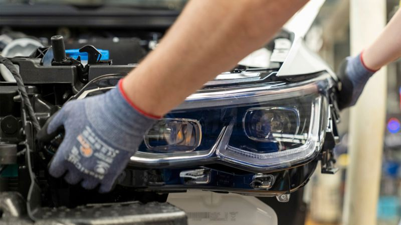 A pair of hands fitting a headlight