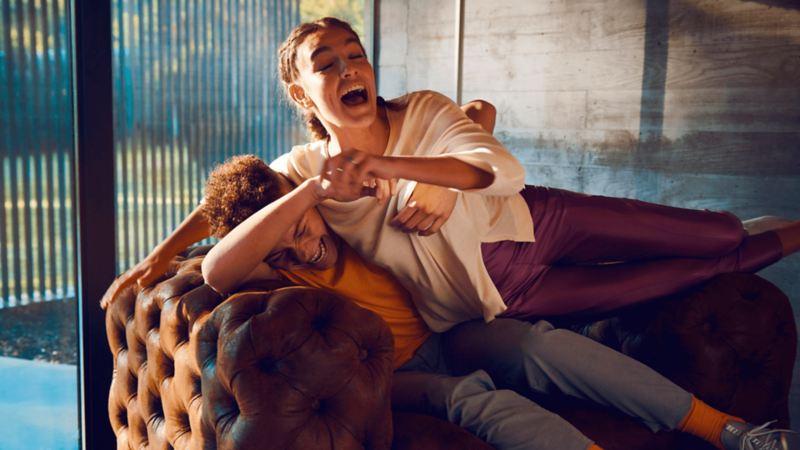 Deux amis jouant sur un divan, lien vers l'article Volkswagen Pulse « Les concessionnaires soutiennent les communautés ».