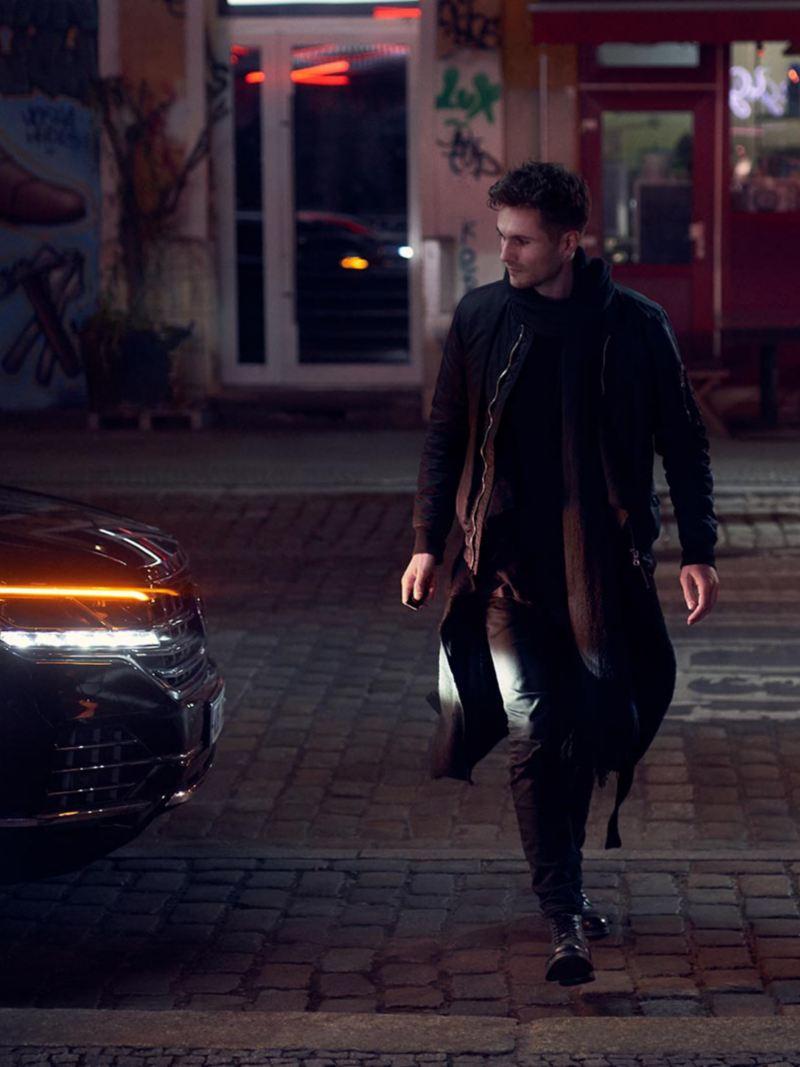 Un hombre cruza la calle en la noche