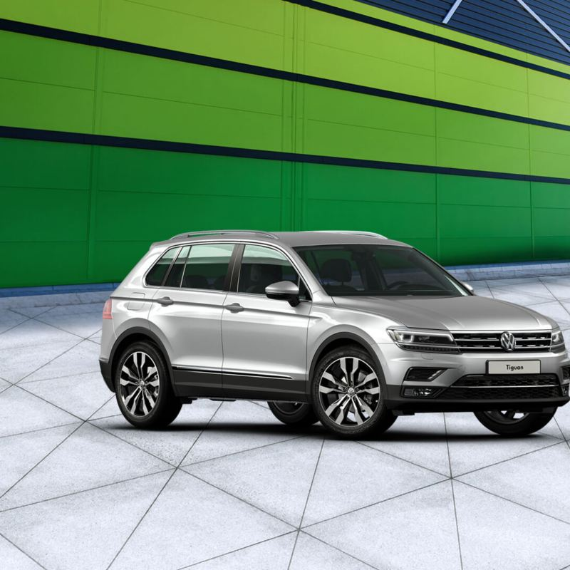A Volkswagen Tiguan in silver driving around a mountain road