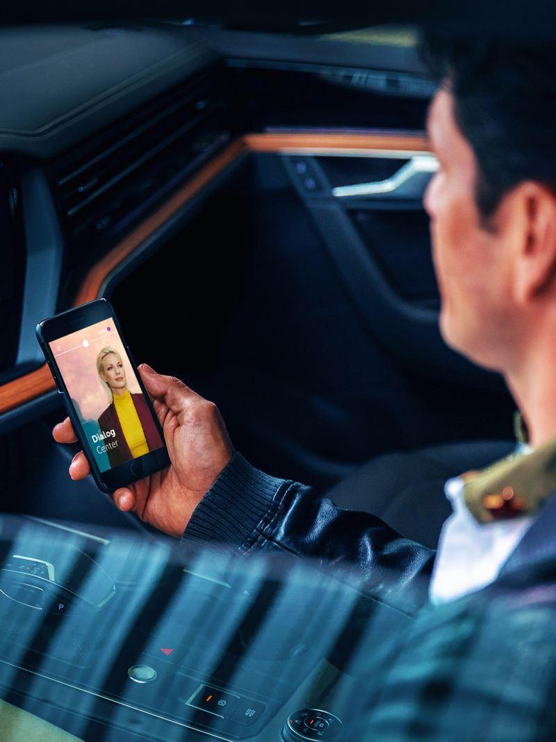 Mann sitzt im Volkswagen und schaut auf sein Smartphone