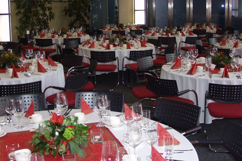 Festlich gedeckter Saal mit roter Bestuhlung