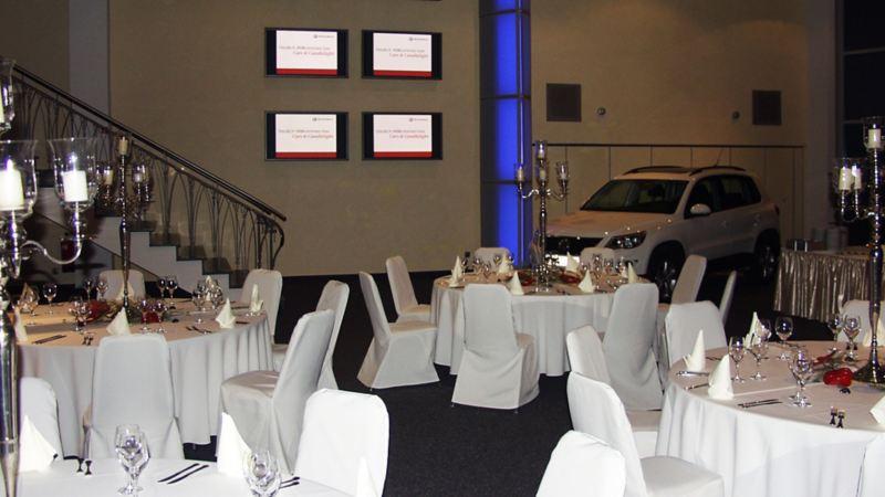 Festsaal mit gedeckten runden Tischen, im Hintergrund steht ein weißer Volkswagen