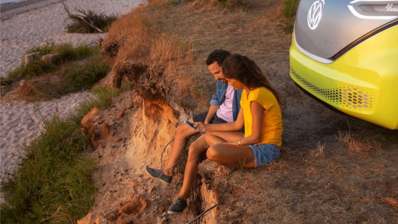 A couple sitting on the edge of a cliff behind their vehicle