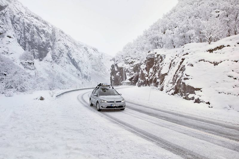 e-Golf with snowboard holder driving through a snowy mountain landscape