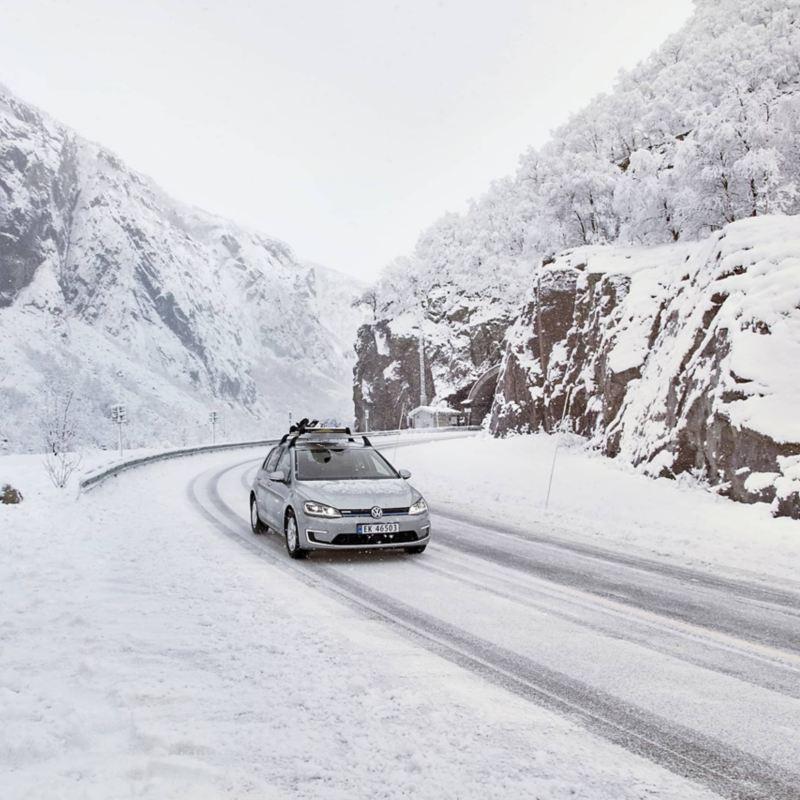 e-Golf mit Snowboardhalter fährt durch eine verschneite Berglandschaft