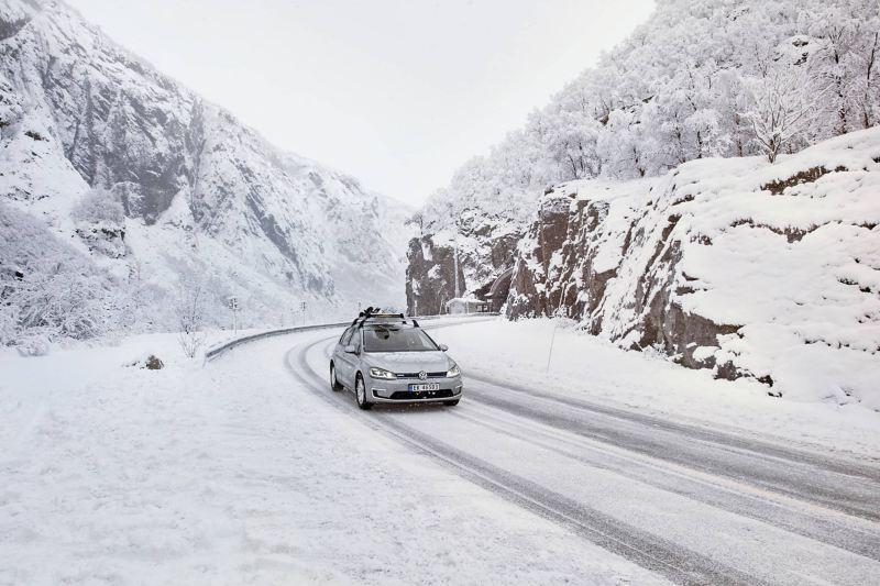 e-Golf com suporte para prancha de snowboard a conduzir através de uma paisagem de montanha com neve