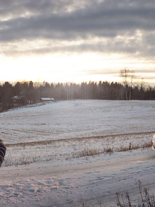 Ginge nằm trên một con đường đất, trong nền là e-Golf của anh ấy